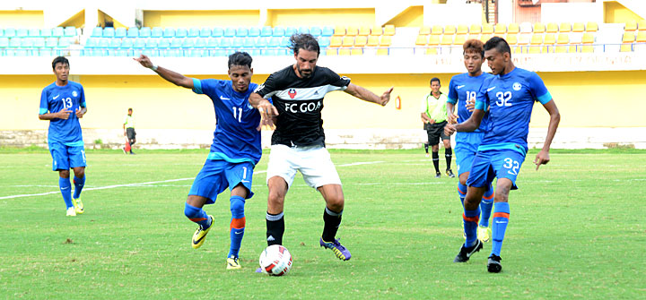 India U 19 players tackle FC Goa's Robert Pires in a friendly match at Tilak Maidan